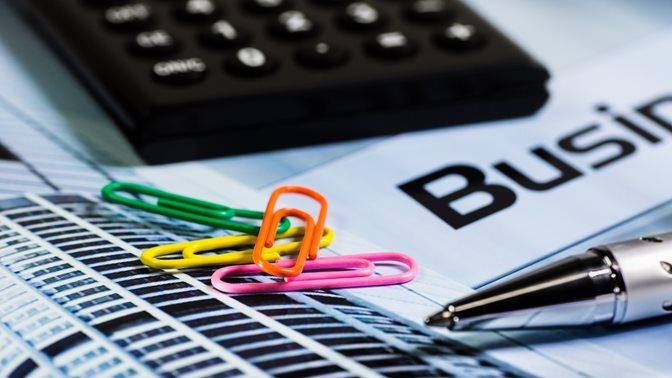 Büroklammern, Rechner und Kugelschreiber